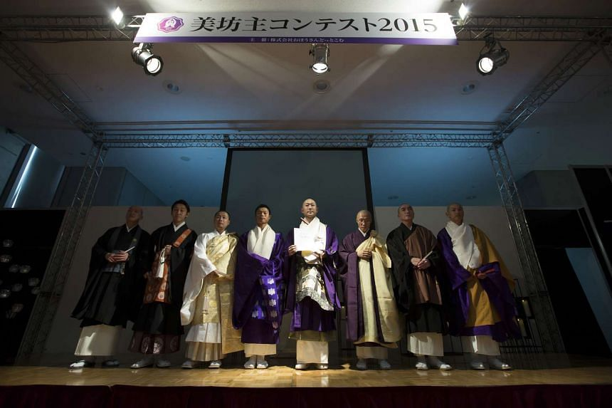 Monks stand on stage during a pageant at the Life Ending Industry Expo on Dec 9, 2015.