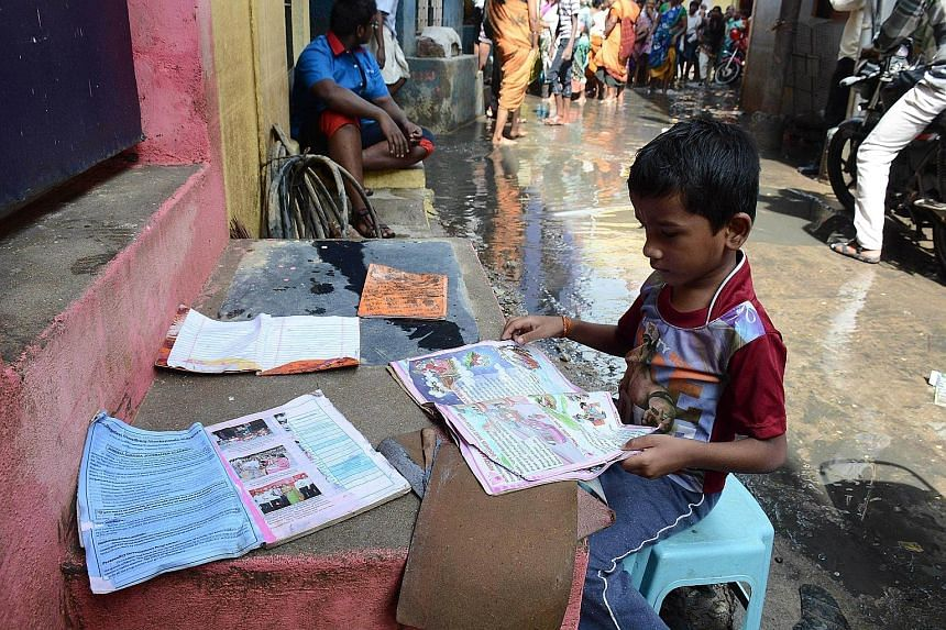 An Indian boy putting out his school books to dry as floodwaters receded in Chennai on Monday. Residents in India's southern Tamil Nadu state are grappling with the aftermath of the devastating floods as the authorities step up relief work, following