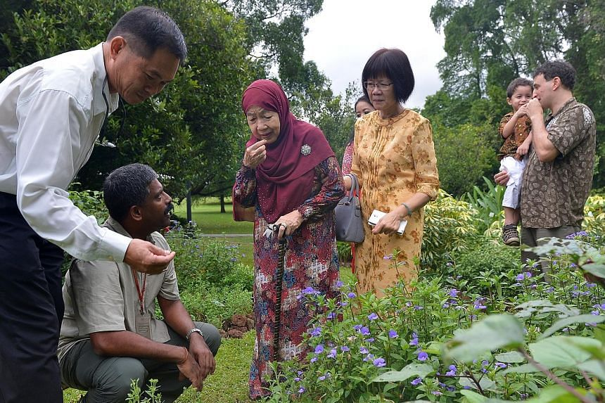 Our Istana - Through The Years features photos from the National Archives of Singapore, SPH, as well as professionals and hobbyists. Madam Noor Aishah (in purple), on a tour of the Istana gardens, along with (from left) Mr Wong Tuan Wah, senior curat
