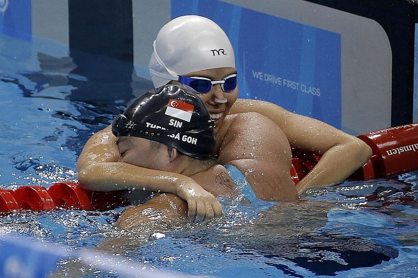 Theresa Goh (black cap) hugging her good friend Yip Pin Xiu after the latter's 50m backstroke S5 (S2-S5) win. Goh was third.