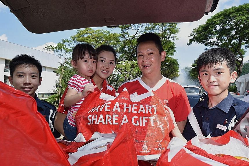 Prudential agent Thomas Lee, 43; his wife Shalyn, 31; and their three-year-old daughter Adelia delivered hampers last Saturday as part of the Boys' Brigade Share-A-Gift project. With them are Boys' Brigade members Lemuel Fan Wenle (left), 14, and Jov