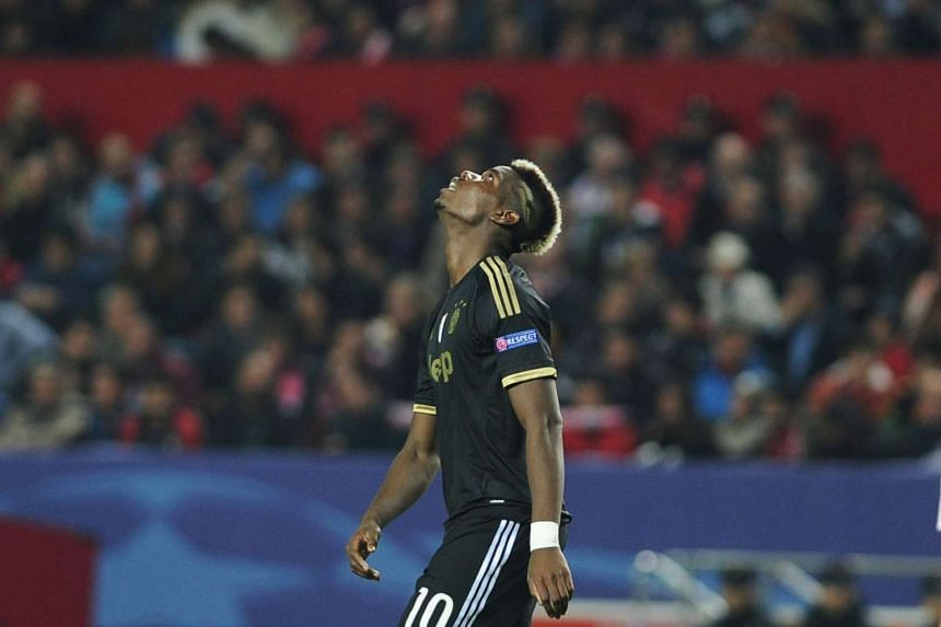 Juventus' French midfielder Paul Pogba reacts after missing a goal opportunity.
