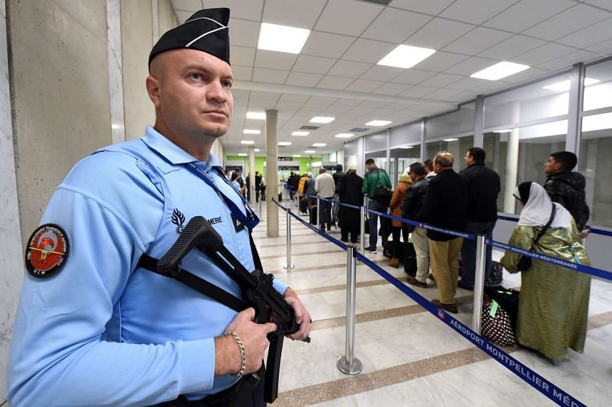 A French Gendarme standing guard as passengers prepare to board a plane at Montpellier airport in southern France, on Nov 20, 2015.