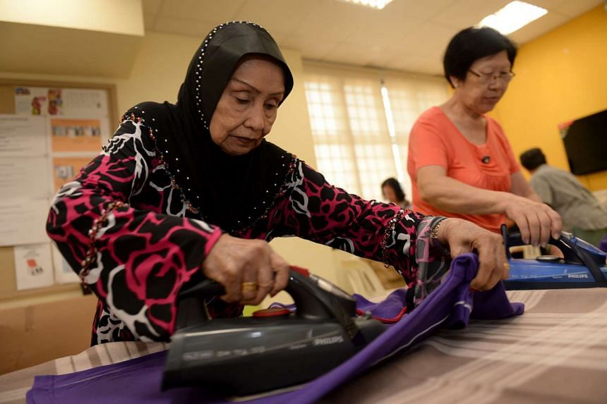 Seniors recruited by the Kembangan-Chai Chee Seniors Activity Centre snip off loose threads from T-shirts, and iron and pack them before they are delivered to customers.