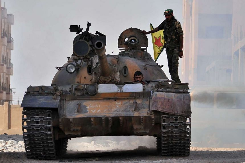 Fighters from the Kurdish People's Protection Units driving a tank through Hasakeh, Syria, on Aug 2, 2015.