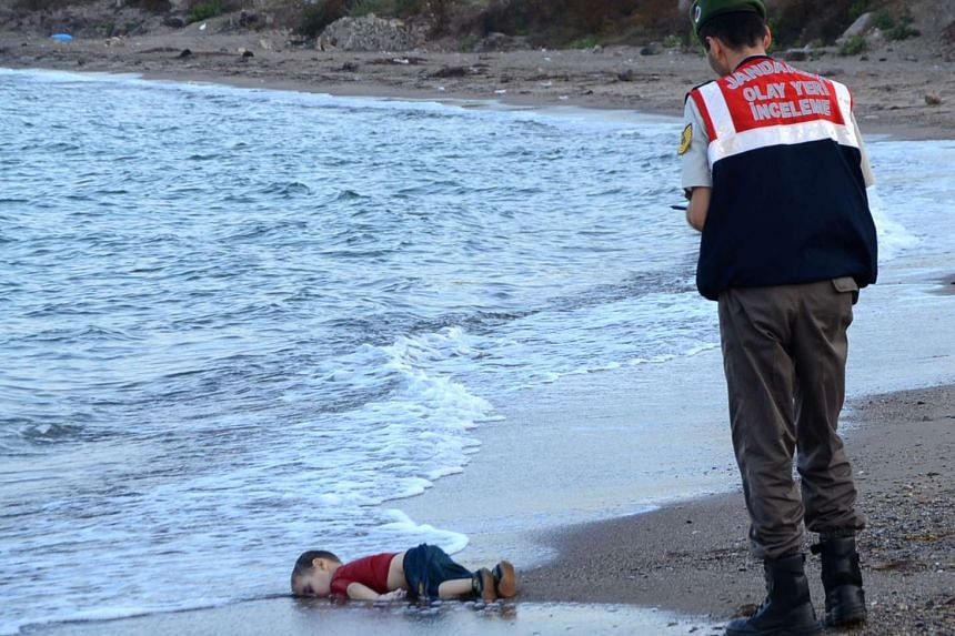 A Turkish police officer stands next to the toddler's body.