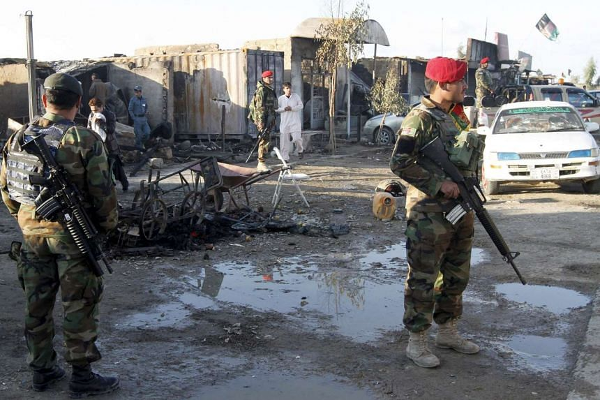 Afghan National Army soldiers standing guard in front of a shop burned during the Taleban attack on Kandahar Airport on Dec 9, 2015.