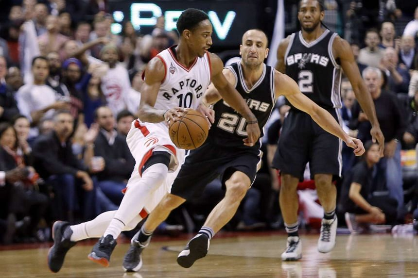 Toronto Raptors guard DeMar DeRozan (white No. 10) dribbling around San Antonio Spurs guard Manu Ginobili at the Air Canada Centre in Toronto on Dec 9, 2015.