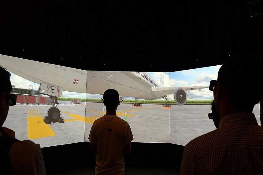 Nanyang Polytechnic students demonstrating how the 3D immersive virtual reality centre provides a virtual airport environment.