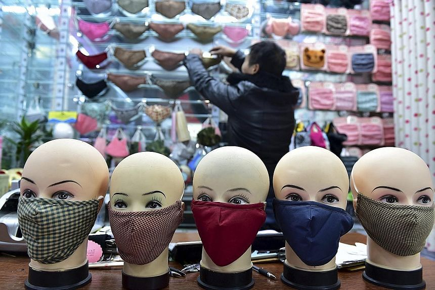 Masks on sale at a shopping mall in Yiwu, Zhejiang province, on Monday. Pollution red alerts have been raised in more cities. Dingzhou and Xinji, two cities in Hebei province, which surrounds Beijing, issued their first red alerts even as the air in