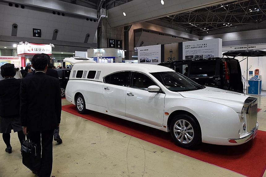 Visitors viewing a Mitsuoka limousine type V hearse on display at the Life Ending Industry Expo 2015 in Tokyo this week. More than 200 companies involved in end-of-life businesses, such as undertakers, are participating in the exhibition.