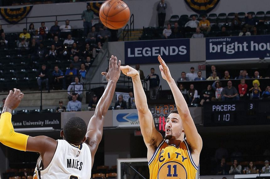 Klay Thompson (right) of the Golden State Warriors shooting against C.J. Miles of the Indiana Pacers in the second half of the game in Indianapolis. The Warriors defeated the Pacers 131-123.