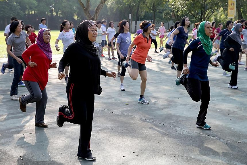 Residents participating in a Bokwa Fitness routine in Choa Chu Kang Park. The cardio-intensive workout, in which participants draw letters of the alphabet and numbers with their feet, is just one of around 16 different types of exercise classes resid