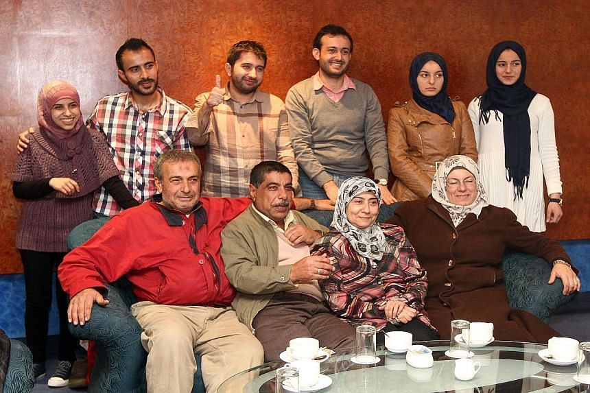 Syrian hairstylists Mohamed Ibrahim (back row, third from left) and Ali Abdul Naser (back row, fourth from left) with their families who arrived in Kuala Lumpur on Tuesday from Turkey. The families are the first batch of Syrians who are in Malaysia a