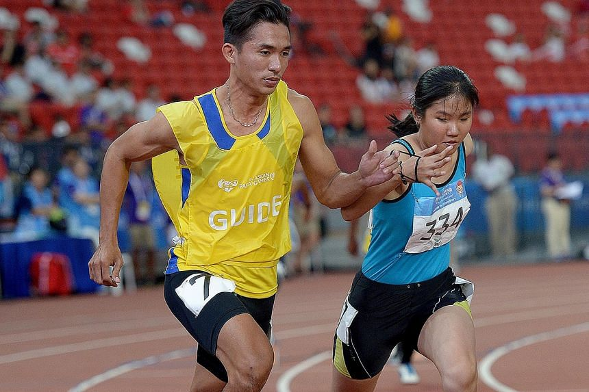 Nguyen Tan Phat (left) of Vietnam, assisting compatriot Nguyen Ngoc Quynh Tram at the Asean Para Games on Tuesday. She is one of three visually impaired runners he has guided for three years.