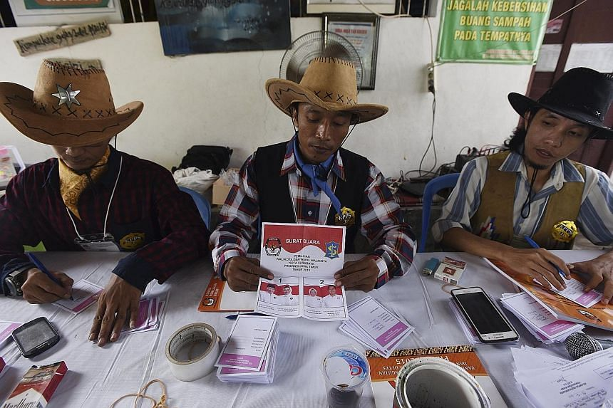 Officials in cowboy costumes preparing ballot slips at a polling station in Surabaya, East Java, yesterday. The decision to hold the regional elections on the same day was aimed at cutting costs and boosting efficiency.