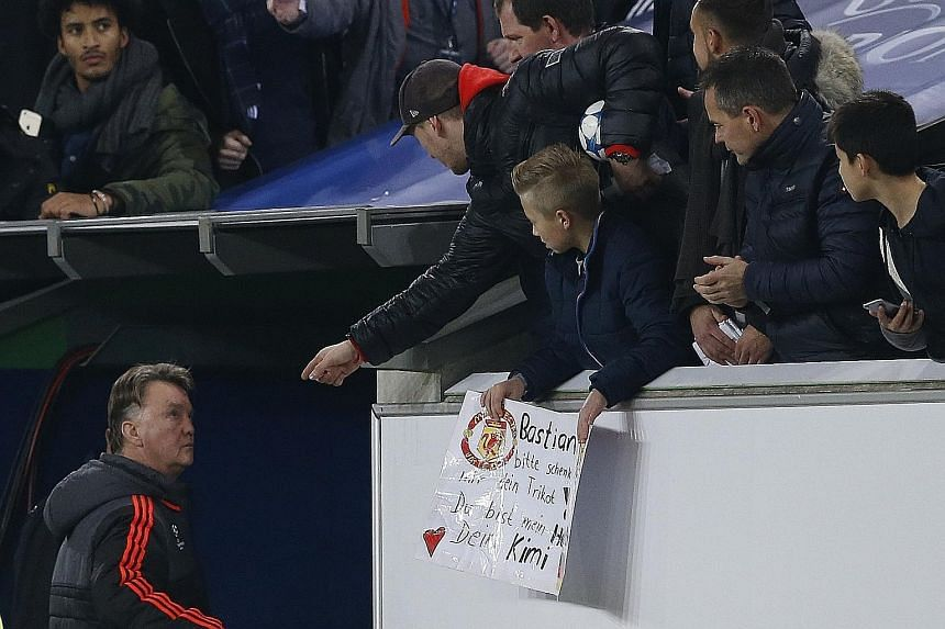 A grim-faced Louis van Gaal looking at downcast Manchester United fans as he walks down the tunnel at the end of the match. Wolfsburg's Naldo (far left) tussling with United's Anthony Martial.