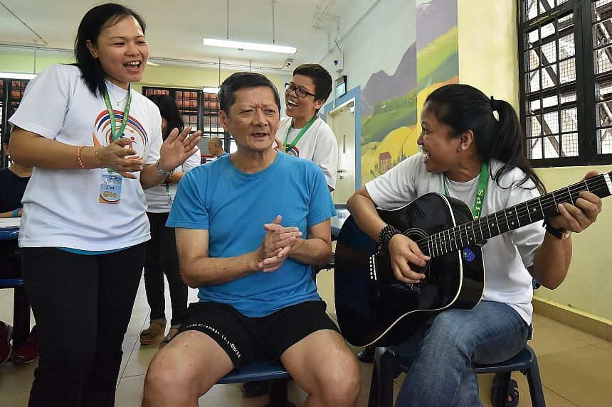 Mr Chua, an IMH patient, enjoying a singing session with volunteers (from left) Margie Agustin, 41, Agnes Juagpao, 41, and Priscilla Manangola, 36. He says he looks forward to the visit from members of the Ladies in the Power of Service volunteer gro