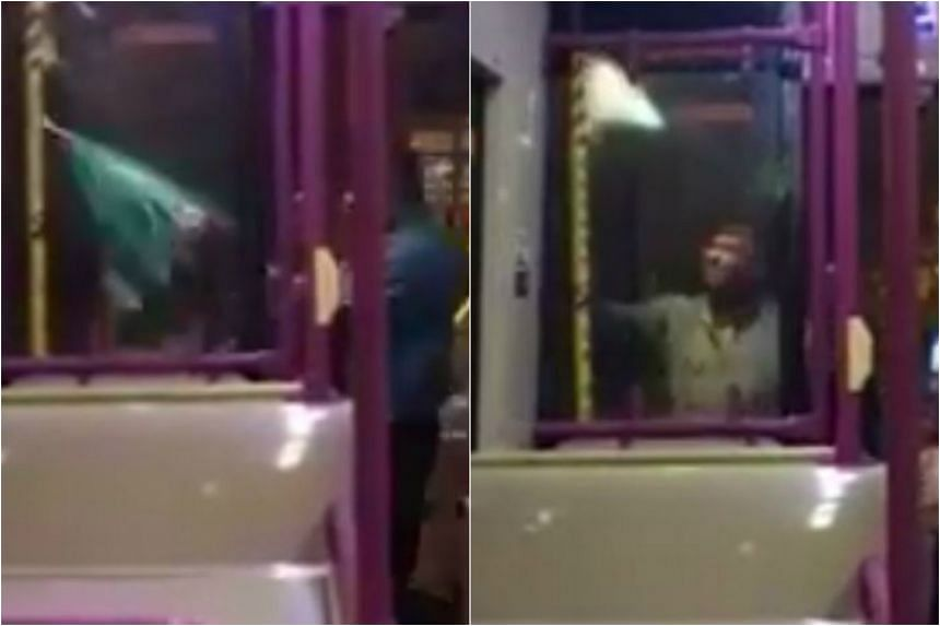 SBS Transit bus driver Terence Jacob using an umbrella to shelter his passengers from the rain.