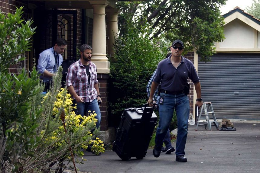 Australian police officers walking down the driveway after searching the home of probable bitcoin creator Craig Steven Wright in Sydney on Wednesday.