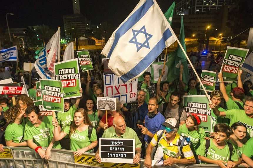 Israeli left-wing activists hold banners and wave their national flag during a rally in Tel Aviv on October.