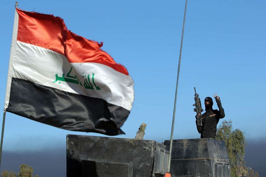 A member of Iraq's counter-terrorism forces gestures as they enter the Tameem district of Ramadi on Wednesday.