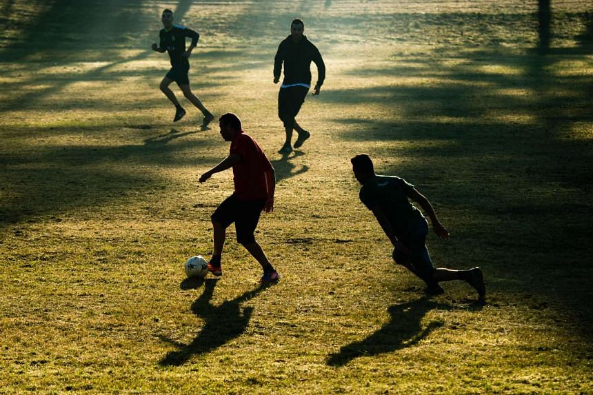 Refugees play football at a shelter for asylum seekers on Nov 3, 2015.