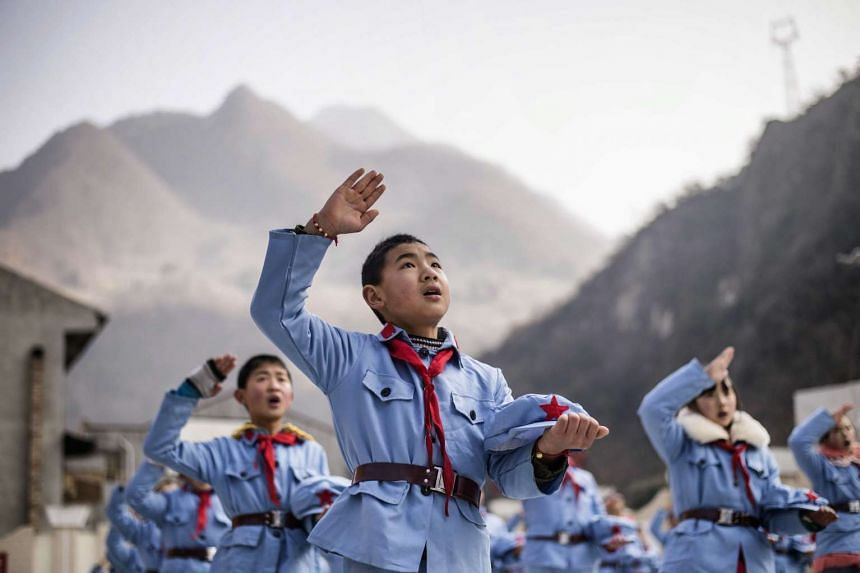 Children dressed in uniform sing after raising the national flag in Beichuan, China.