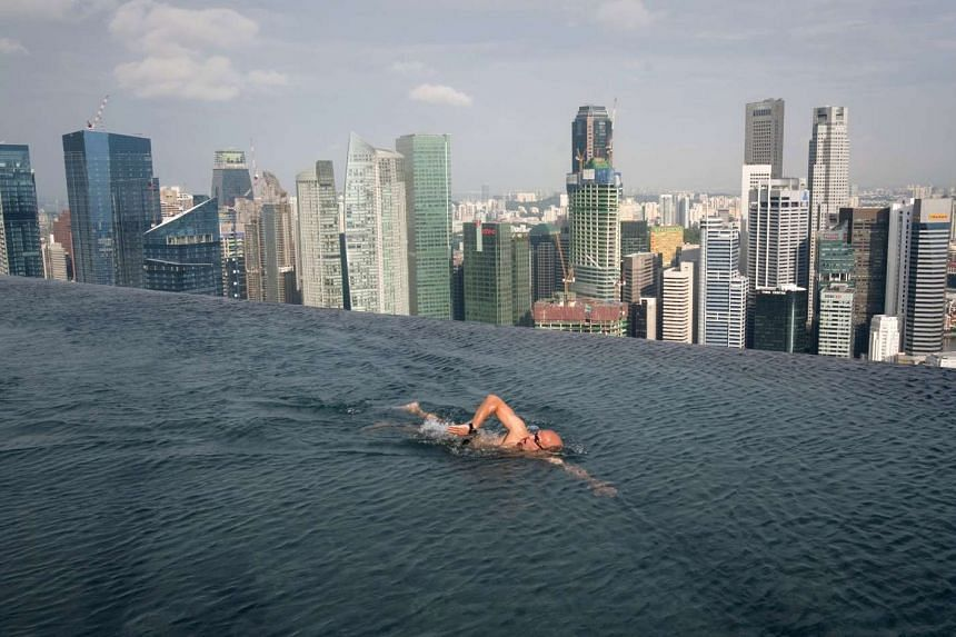 A guest swims in the infinity pool that tops the Marina Bay Sands hotel towers in Singapore.
