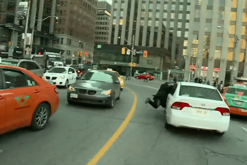 A taxi driver in Toronto protested mobile taxi app Uber by clinging into a moving car.
