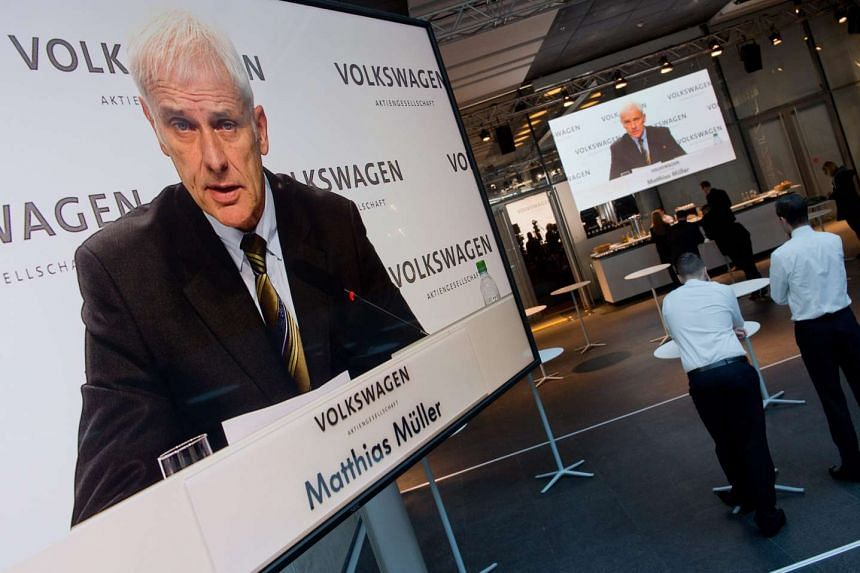 Volkswagen chief Matthias Mueller is pictured on screens during the company's press conference.