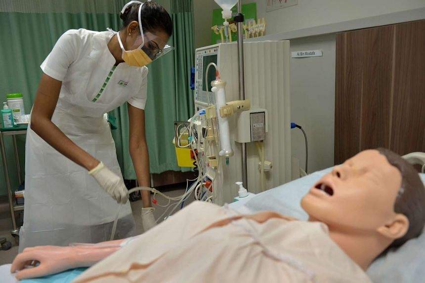 A nurse giving a demonstration on the infection control measures taken when a patient undergoes dialysis.