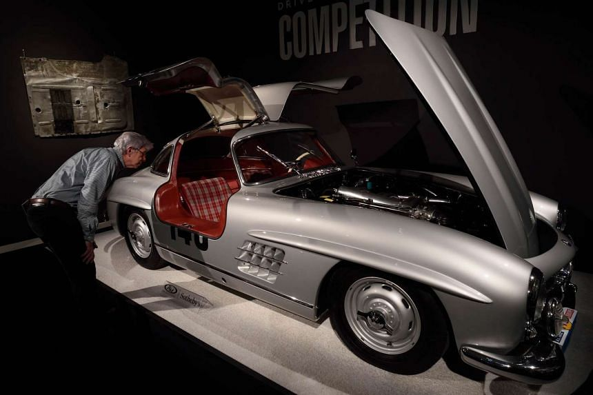 A man views a 1955 Mercedes-Benz 300 SL 'Sportabteilung' Gullwing exhibited at Sotheby's on Dec 9 in New York.