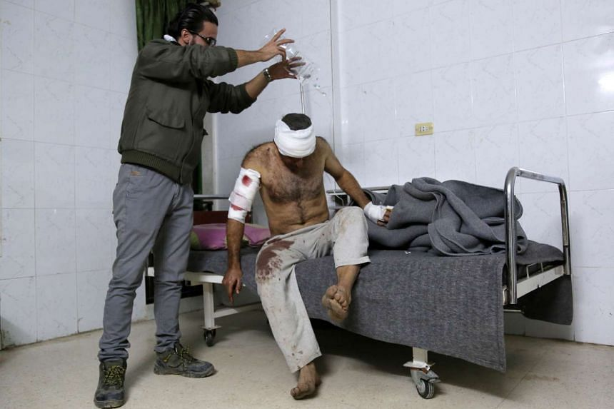 A Syrian man, wounded in a suicide car bomb attack in the nearby town of Tal Tamr, sits on a hospital bed.
