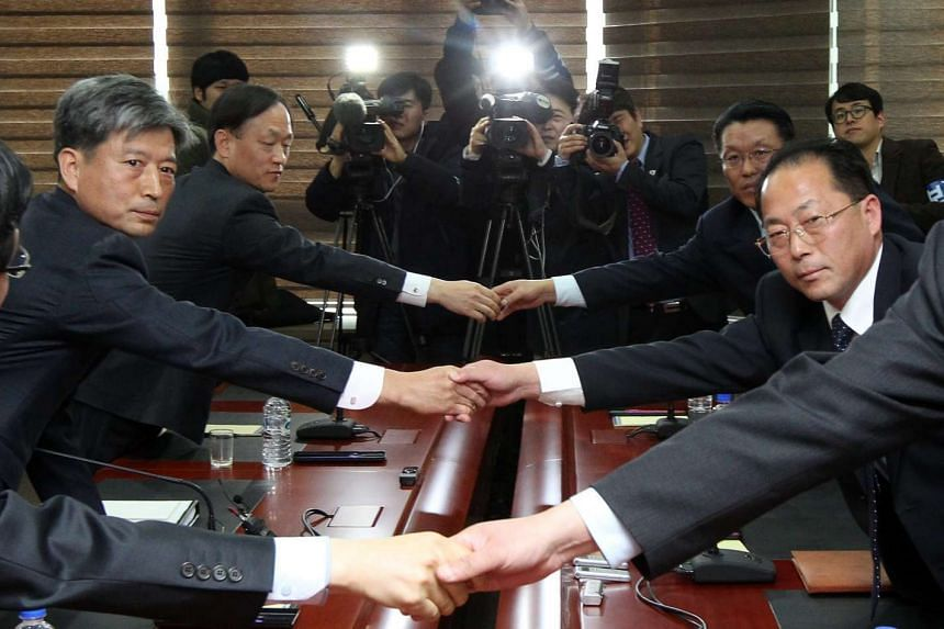 South and North Korean representatives to inter-Korean talks shake hands at the start of their meeting.