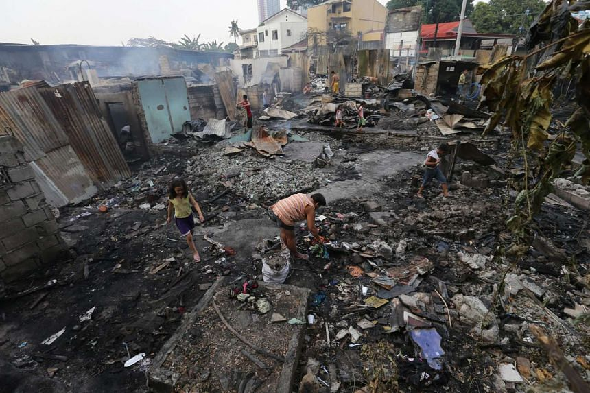 Filipinos search for salvageable materials following a fire in Quezon City, northeast of Manila.