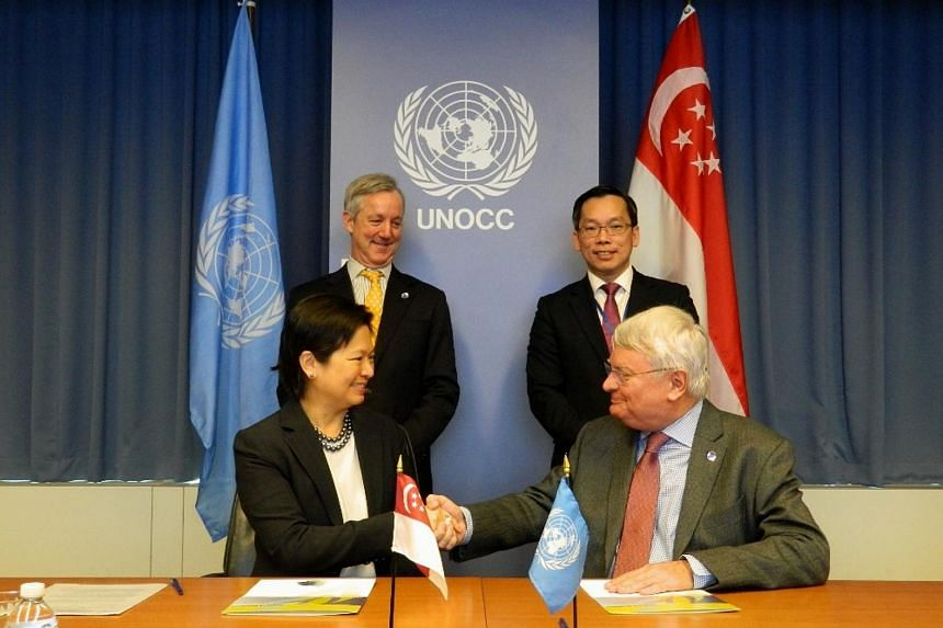The signing of the MOU by Permanent Representative of Singapore to the United Nations, Ms Karen Tan (front, left), and the United Nations Under-Secretary-General for Peacekeeping Operations, Hervé Ladsous (front, right).