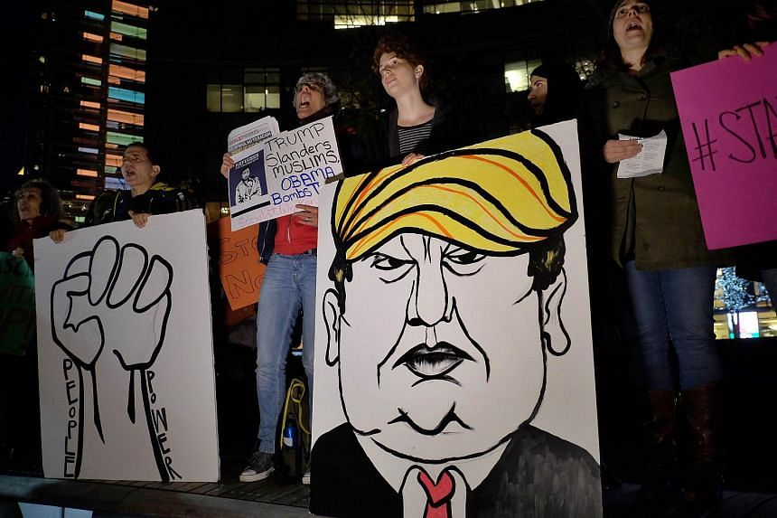 People holding a placard depicting US presidential hopeful Donald Trump at a demonstration in New York on Dec 10.