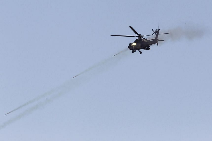 An Apache helicopter firing rockets during Exercise Forging Sabre.