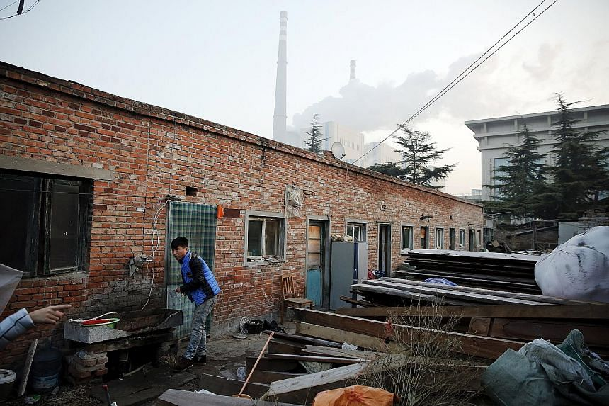 A worker brushing his teeth outside his dwelling, which is next to a coal power plant, in Beijing during smog-free weather yesterday, which was the day the city's red-alert measures expired.
