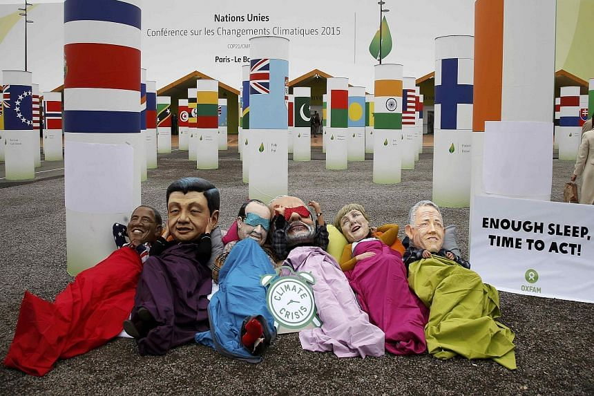 Activists from anti-poverty charity Oxfam protesting outside the talks venue while wearing masks depicting (from left) US President Barack Obama, Chinese President Xi Jinping, French President Francois Hollande, India's Prime Minister Narendra Modi,