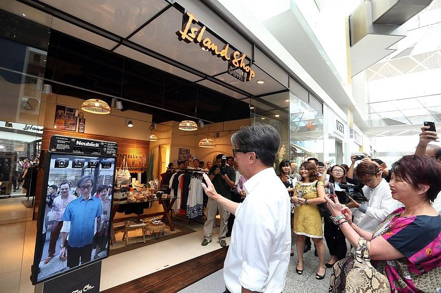 "Manpower Minister Lim Swee Say ""trying on"" clothes using a device outside Island Shop at Clarke Quay yesterday. Mr Lim had launched a manpower plan to help retailers attract talent and increase productivity."