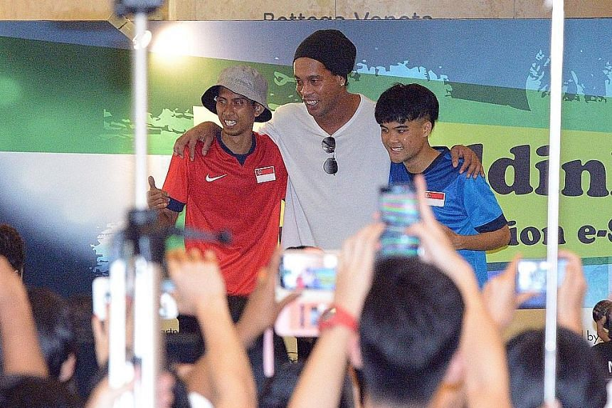 Ronaldinho posing with his fans (left) at Ion Orchard as he launched his E-scooter brand together with his football academy. The player, known for his dribbling skills and deft flicks, leaving Ion Orchard on a chauffeured Rolls Royce (left).