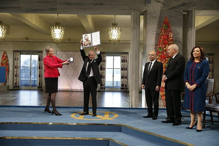 Ms Kaci Kullmann Five (in red) presenting the diploma and medallion to the winners of the 2015 Nobel Prize, the Tunisian National Dialogue Quartet. Representing the organisations in the quartet are (from left) General Labour Union secretary-general H