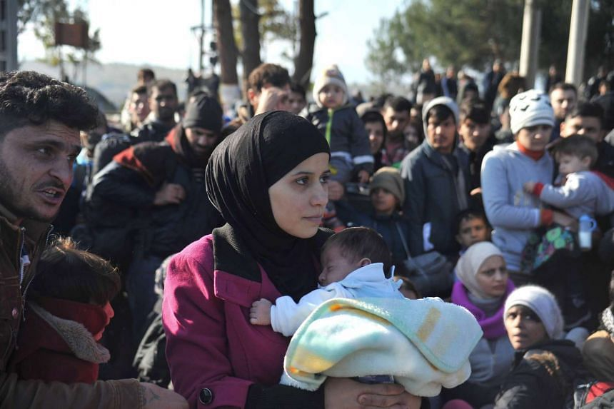 Migrants and refugees wait to cross the Greek border on Dec 5, 2015.