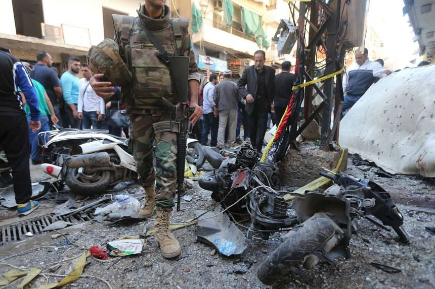 A Lebanese soldier walking past damaged motorbikes at the site of the two explosions in Beirut on Nov 13.