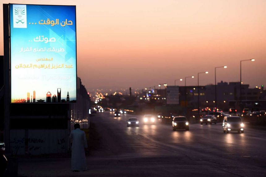 Cars going past a candidate's campaign billboard in the al-Sahafa district of Riyadh on Dec 1.