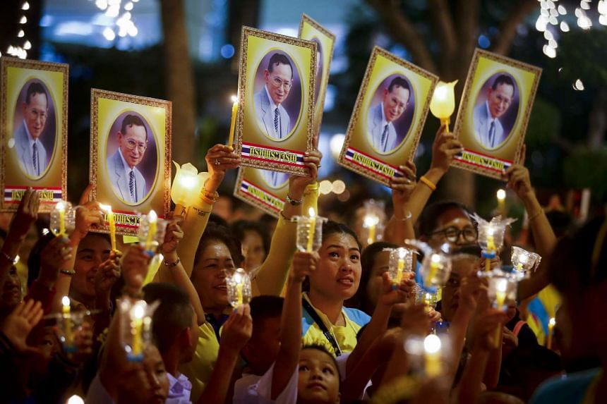 Thai well-wishers light candles and hold up portraits of Thai King Bhumibol Adulyadej during celebrations on his 88th birthday.