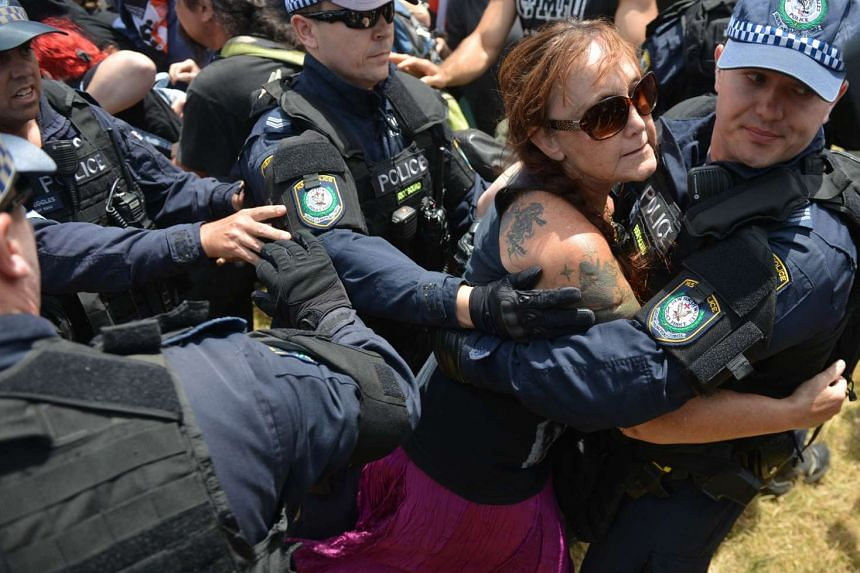 A woman is held back by police after she tried to confront demonstrators.