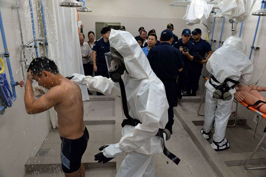A demonstration of an infected person being treated in the decontamination chamber.